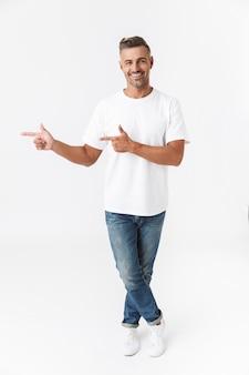 Полнометражный портрет красивого случайного человека, стоящего изолированно на белом, представляя пространство копии, указывая