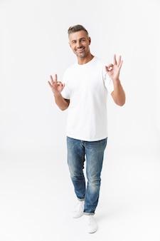 白で隔離されて立っているハンサムなカジュアルな男の完全な長さの肖像画、大丈夫を示しています