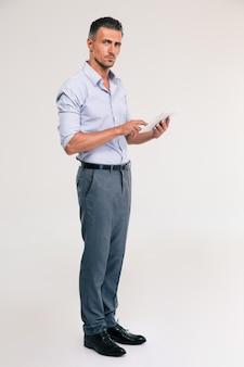 Полнометражный портрет красивого человека с помощью изолированного планшетного компьютера. глядя в камеру