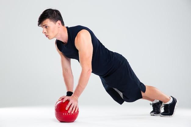 分離されたフィットネス ボールでハンサムな男のトレーニングの完全な長さの肖像画