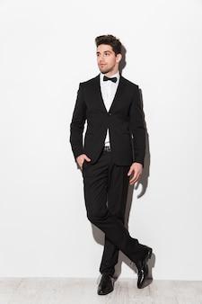 Полный портрет красивого молодого человека в черном костюме с луком, стоящего изолированно над белой, позирует