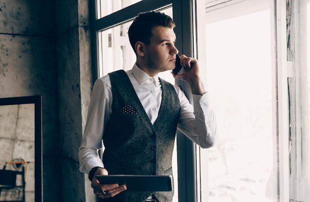 Полный портрет красивого молодого владельца, глядя около окна во время разговора по телефону, держа планшет в своем офисе.