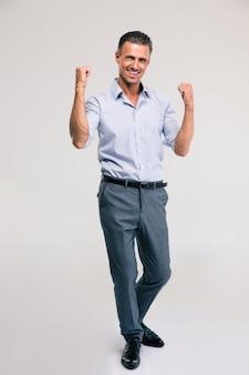 Портрет в полный рост счастливого бизнесмена, празднующего свой успех в сером пространстве