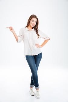 白い壁に分離された指を離れて指している幸せなカジュアルな女性の完全な長さの肖像画
