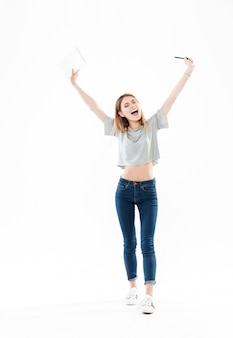 メモ帳を保持している幸せな陽気な女の子の完全な長さの肖像画