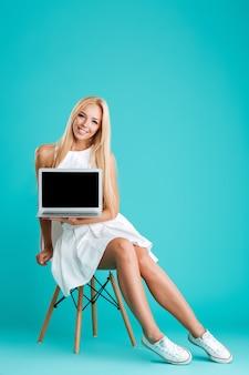椅子に座って、青い背景で隔離の空白の画面のラップトップを示す幸せな陽気な女性の完全な長さの肖像画