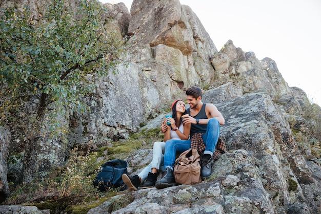 山でハイキングしながら休んでいる幸せなカップルの完全な長さの肖像画