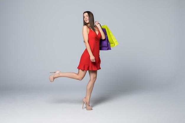 白い壁に分離されたカラフルなショッピングバッグを立って保持している赤いドレスを着て幸せな興奮した女性の全身像