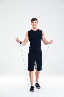 Полный портрет счастливой тренировки человека фитнеса с изолированной скакалкой