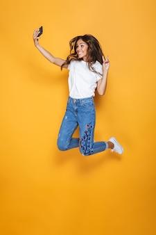 Портрет в полный рост счастливой девушки с длинными темными волосами, перепрыгивающей через желтую стену и делающей селфи