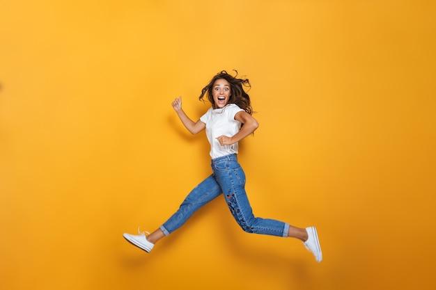 Портрет счастливой девушки с длинными темными волосами в полный рост, перепрыгивающей через желтую стену