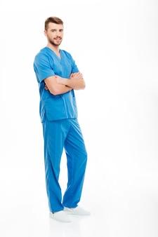 白い背景で隔離の腕を組んで立っている幸せな男性医師の完全な長さの肖像画