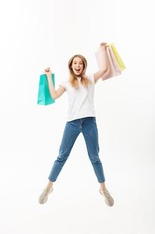 ジャンプして白い背景で隔離のカメラを見ながら買い物袋を保持している幸せなかわいい女の子の完全な長さの肖像画。