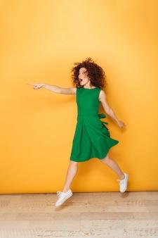 ドレスで幸せな赤毛の女性の完全な長さの肖像画
