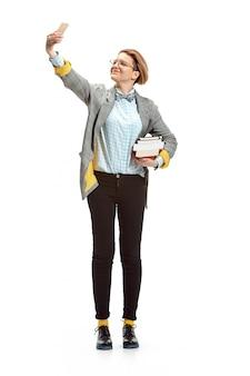 공백에 고립 된 책을 들고 행복 하 게 웃는 여자 학생의 전체 길이 초상화