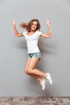 Полнометражный портрет счастливой улыбающейся женщины, прыгающей и показывающей жест v, изолированной на серой стене