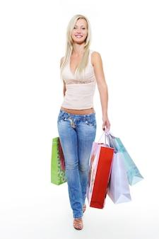 Портрет счастливой идущей девушки с хозяйственными сумками в полный рост
