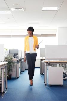 사무실에서 걷는 행복 한 여자의 전체 길이 초상화