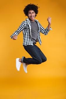 Полнометражный портрет счастливого молодого африканского человека скача