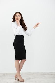 Полнометражный портрет счастливой молодой бизнес-леди с очками, стоящими и указывающими пальцем на изолированное пространство копии