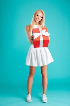 Портрет счастливой молодой девушки в полный рост, показывающий подарочную коробку, изолированную на синем фоне