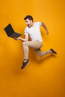 Полный портрет счастливого молодого человека прыгает