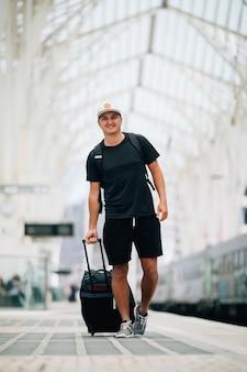 駅でスーツケースを持って歩く幸せな若い男の全身像