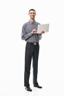 노트북 컴퓨터를 들고 흰색 위에 서있는 격자 무늬 셔츠를 입고 행복 한 젊은 남자의 전체 길이 초상화