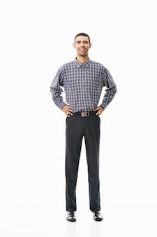 흰색 위에 서있는 격자 무늬 셔츠를 입고 행복 한 젊은 남자의 전체 길이 초상화