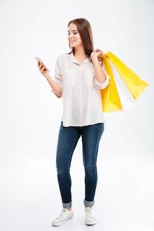 白い壁に隔離された買い物袋と携帯電話を保持している幸せな若い女性の完全な長さの肖像画