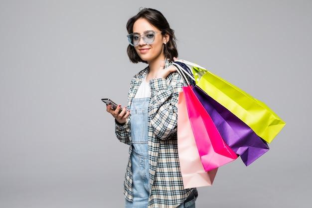 Портрет счастливой молодой женщины в полный рост, держащей сумки и мобильный телефон изолированы