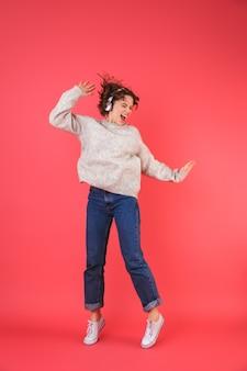 ピンクの上に分離された幸せな若い女性の全身像