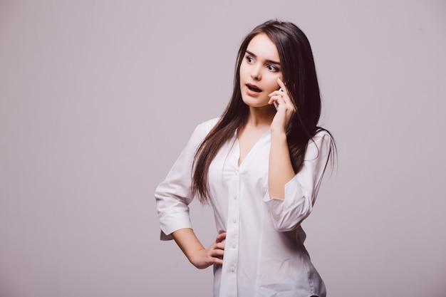 白い背景で隔離の電話で話している幸せな若い女性の完全な長さの肖像画