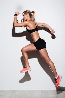 健康的な筋肉スポーツウーマンジャンプの完全な長さの肖像画