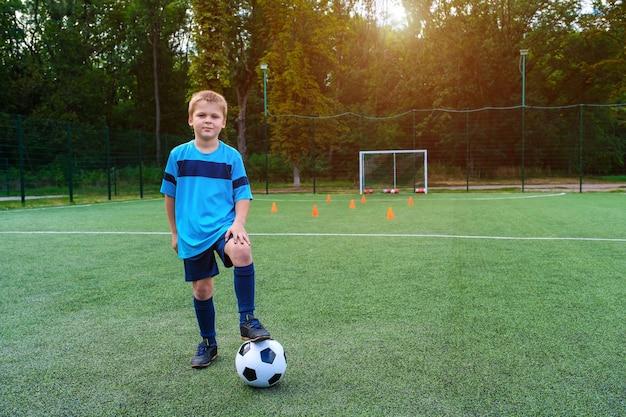 Портрет в полный рост ребенка в спортивной одежде, позирующего с футбольным мячом на открытом воздухе
