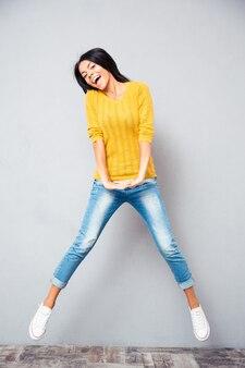 Портрет смеющейся прыгающей женщины в полный рост
