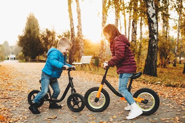 Портрет в полный рост прекрасной маленькой девочки и ее брата, играющих со своими велосипедами лицом к лицу в парке.