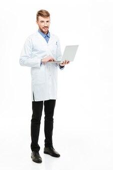 ラップトップコンピューターを保持し、白い背景で隔離のカメラを見ている男性医師の全身像