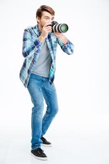 흰색 배경에 고립 된 사진 카메라에 총을 만드는 남성 사진 작가의 전체 길이 초상화