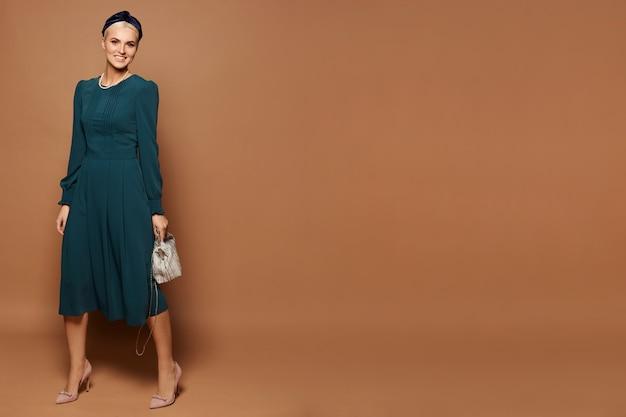 긴 소매와 미디 사이즈 드레스를 입고 금발 머리를 가진 모델 여자의 전신 초상화