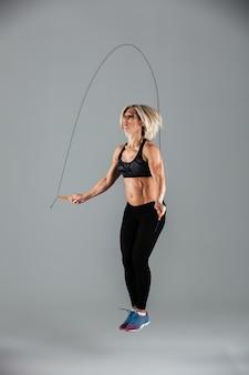 근육 성인 sportswoman 점프의 전체 길이 초상화