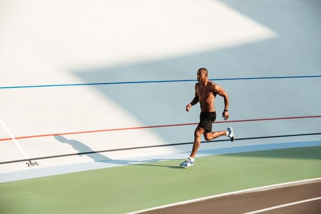 筋肉の半分裸のスポーツマンの完全な長さの肖像画