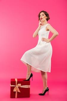 Полная длина портрет задумчивой девушки, одетой в платье