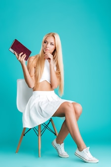 Портрет задумчивой молодой женщины, держащей книгу в полный рост, сидя на стуле, изолированном на синем фоне