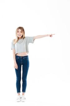 立っているかなりカジュアルな若い女性の完全な長さの肖像画