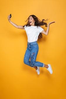 Портрет красивой девушки с длинными темными волосами в полный рост, перепрыгивающей через желтую стену и делающей селфи