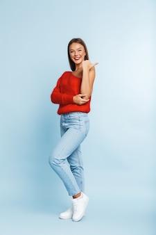 Портрет красивой молодой девушки в полный рост, указывая пальцем в сторону