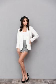 회색 배경 위에 서있는 미니 스커트와 재킷을 입은 예쁜 젊은 여자의 전체 길이 초상화