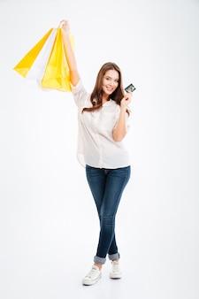 白い壁で隔離の買い物袋と銀行カードを保持しているかなり若い女性の全身像