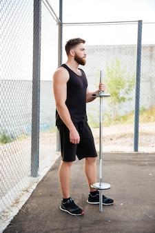 屋外に立っている間バーベルを保持している深刻なひげを生やしたスポーツマンの全身像